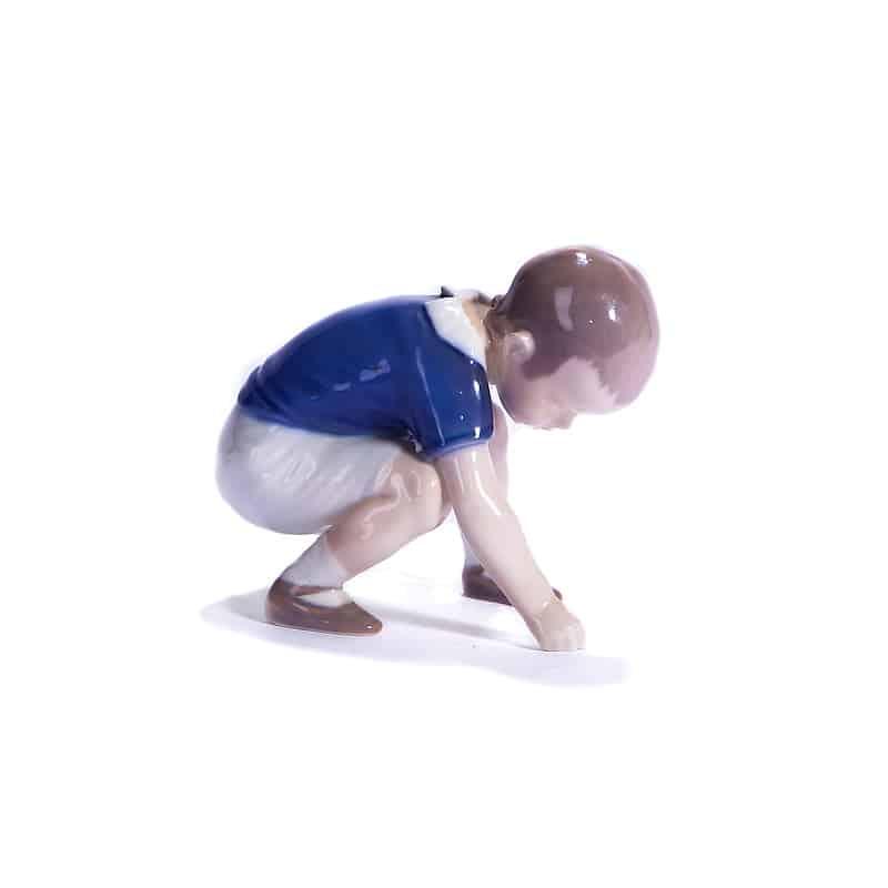 Мальчик на корточках рисует